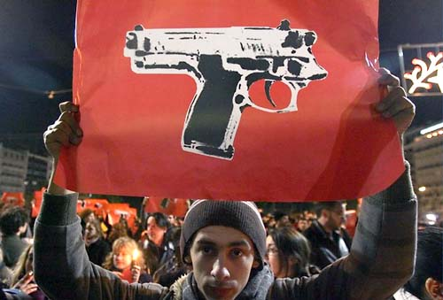 Youth holds posters depicting a gun in front of riot police deployed in front of Greek Parliament late December 9, 2008 during a peaceful demonstration following the death of a 15years-old boy shot by a policeman.