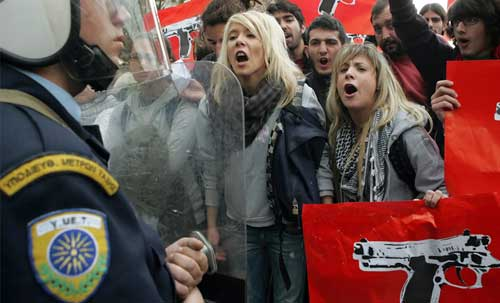 Students shout at riot police outside the police headquarters during a demonstration in Athens on December 15, 2008.