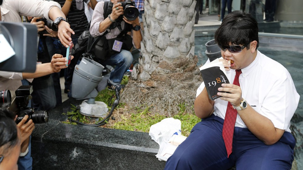 Man reading 1984 in Thailand, being documented by cellphones.